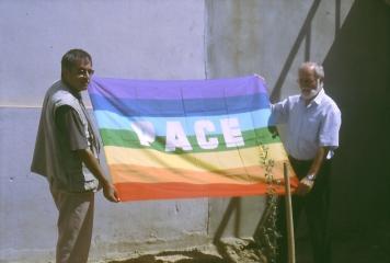 Horst Oberkampf (r.) übergibt Rommel Moushi, dem Direktor von AAS, eine Friedens Fahne